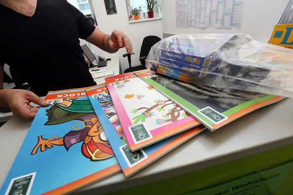 BERLIN, GERMANY - AUGUST 05: An employee unpacks donated coloring books and watercolors for children at a temporary home providing assistance for refugees on August 5, 2015 in Berlin, Germany. Since the beginning of the year, around 300,000 refugees, most recently predominently from Iraq, Syria, and Afghanistan, have registered as asylum seekers in the country, a figure with which the country has been struggling to cope, particularly on state levels. Although one billion euros ($1.1 billion) have been pledged from the government to assist in the matter this year, critics say that figure should be doubled. Meanwhile right-wing extremists have demonstrated against the arrival of the refugees, particularly in smaller towns. (Photo by Adam Berry/Getty Images)