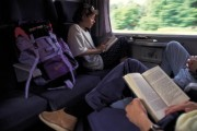Youngs backpackers Two young backpackers reading a book in the compartment of a train while they´re going to Germany