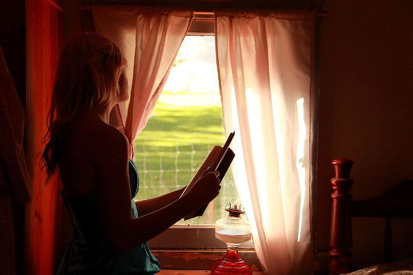 Girl Holding Book Looking Out Window free creative commons